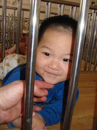 Sweet Chinese orphan smiling in a 'crib room'.