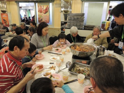 Mr. Au & family eating at the Pun Choy with volunteers & other guests.