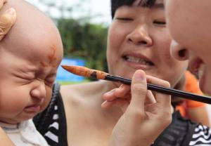 Painting a child with wine to avoid ghosts at the Nanshan Mountain scenic zone.
